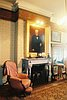 Library of Asahel Bush House Museum showing 1880 William Cogswell portrait of Asahel Bush II hanging above original marble fireplace.