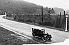 Car drives along straight stretch of Terwilliger Blvd. before it was paved.